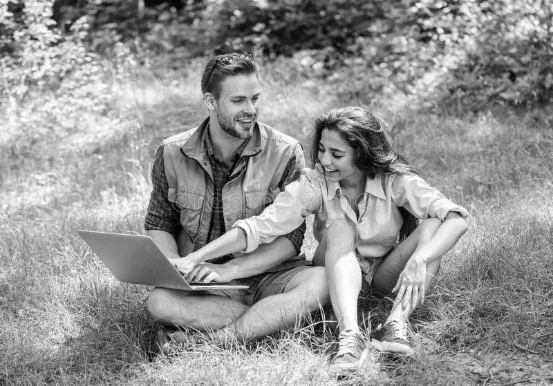 Молодость пар тратит отдых outdoors с компьтер-книжкой Современные технологии дают возможность быть онлайн и работу в любых стоковое фото