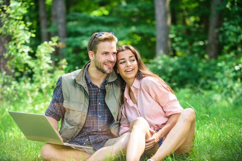 Молодость пар тратит отдых outdoors с компьтер-книжкой Человек и девушка работая с компьтер-книжкой на зеленом луге самомоднейшие стоковое изображение