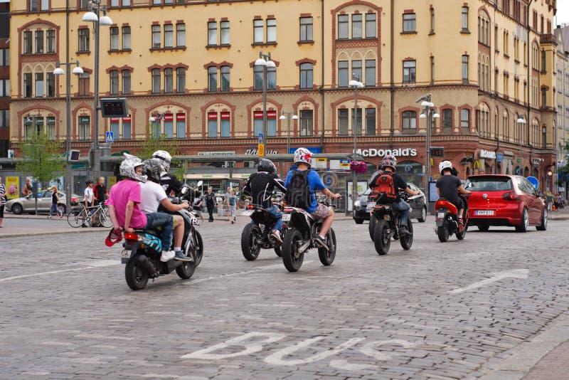 Молодость управляя самокатами moto в городе Tampere стоковые изображения