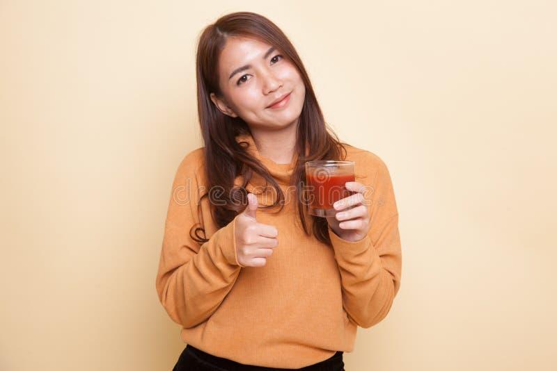 Молодые азиатские большие пальцы руки женщины вверх с соком томата стоковая фотография rf