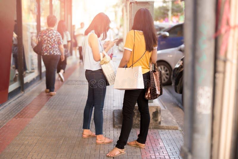 Молодые азиатские девушки держа хозяйственные сумки используя сотовый телефон стоковые изображения