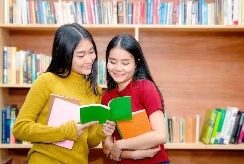 Молодые азиатские книги чтения студента колледжа в острословии библиотеки стоковая фотография rf