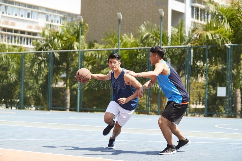 Молодые азиатские люди играя баскетбол стоковые фотографии rf