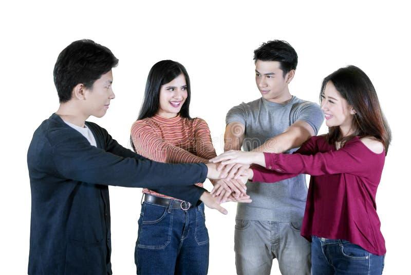 Молодые азиатские люди присоединиться к их рукам на студии стоковая фотография