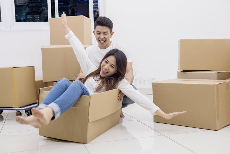 Молодые азиатские пары ехать в картонной коробке стоковые изображения