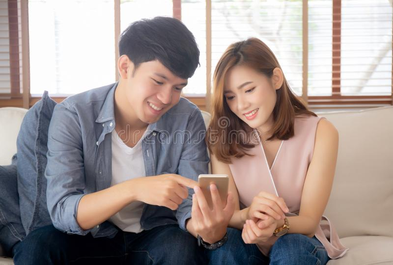Молодые азиатские пары или друг выглядя умным мобильным телефоном с наслаждаются на живущей комнате стоковые изображения