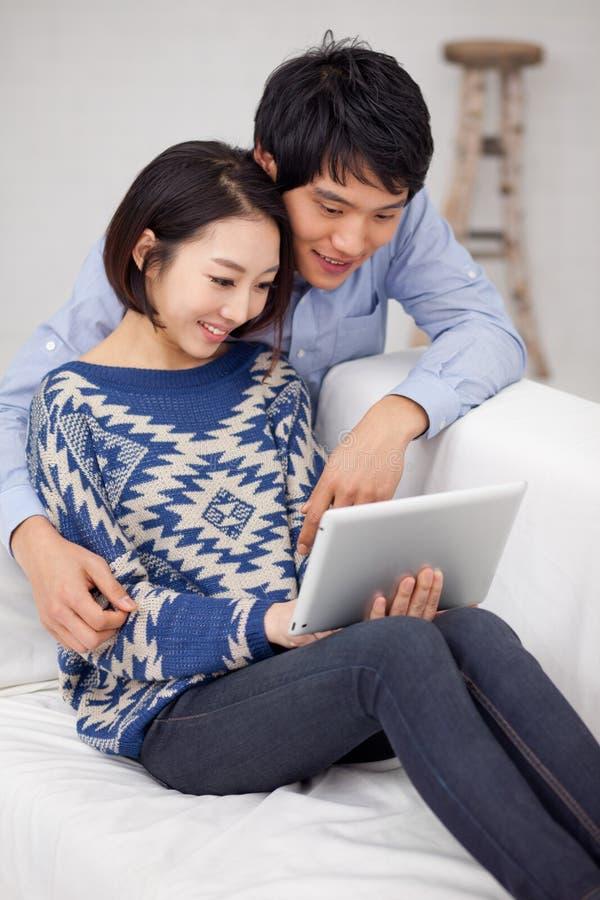 Молодые азиатские пары используя ПК пусковой площадки стоковые изображения rf