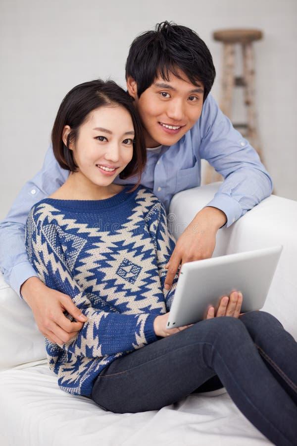 Молодые азиатские пары используя ПК пусковой площадки стоковые изображения