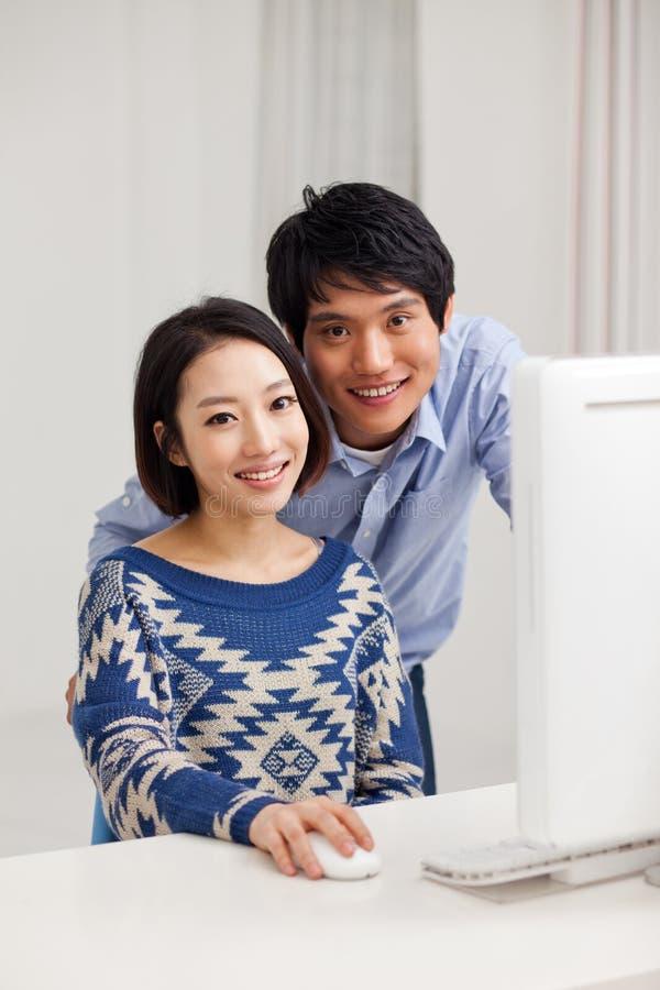 Молодые азиатские пары используя ПК стоковое фото