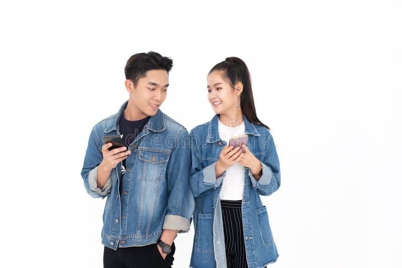 Молодые азиатские пары используя смартфон на белой предпосылке стоковая фотография rf