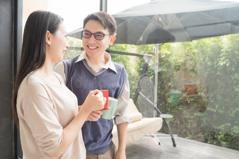 Молодые азиатские пары ослабить с кофе на современном доме внутри помещения смотря снаружи стоковое фото rf