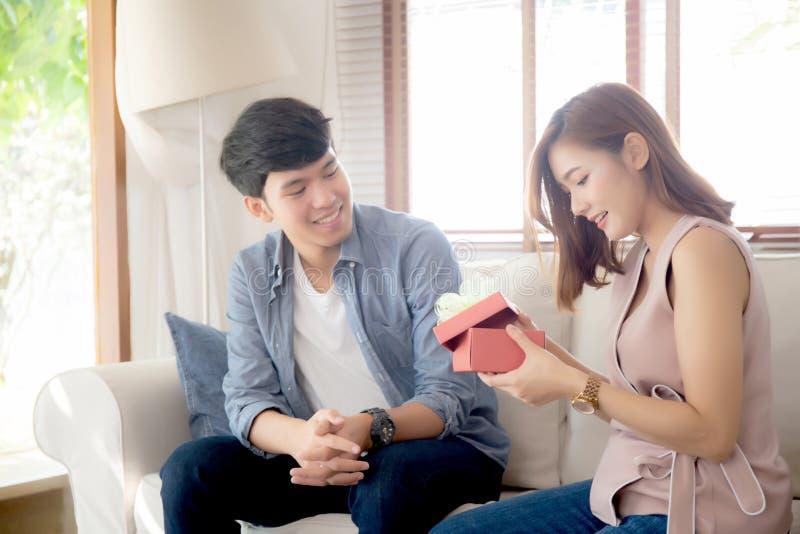 Молодые азиатские пары празднуют день рождения совместно, человек Азии давая настоящий момент подарочной коробки женщине для сюрп стоковое фото