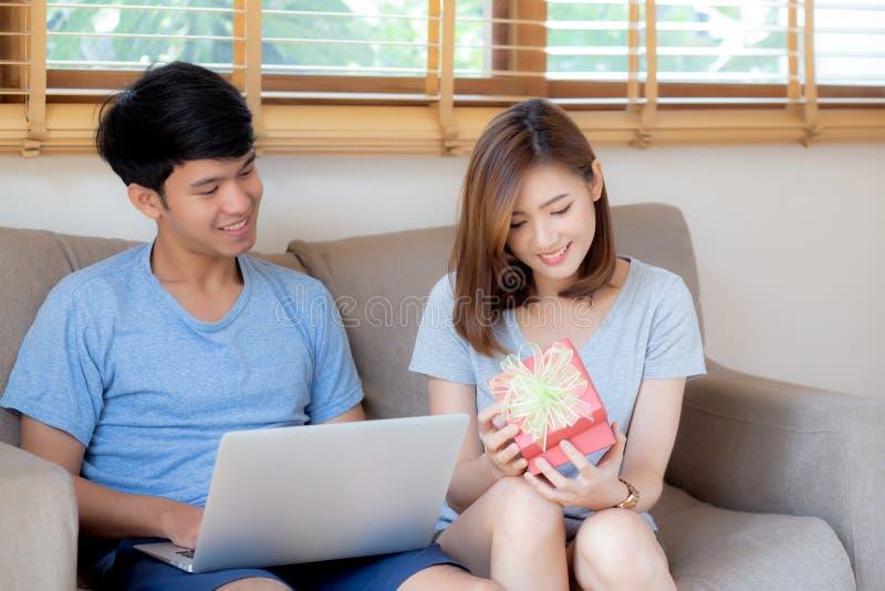 Молодые азиатские пары празднуют день рождения совместно, человек Азии давая настоящий момент подарочной коробки женщине для сюрп стоковая фотография