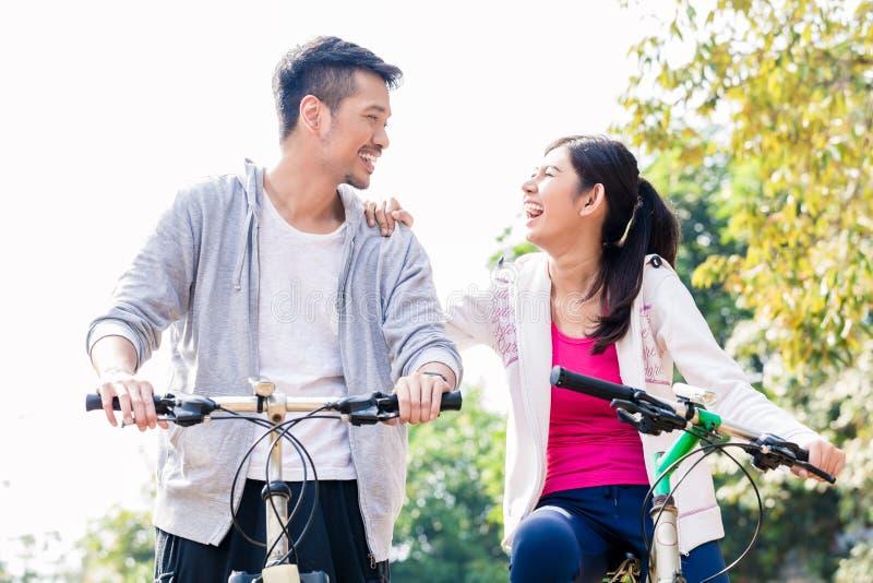 Молодые азиатские пары смеясь над совместно пока ехать bicycles стоковые фотографии rf