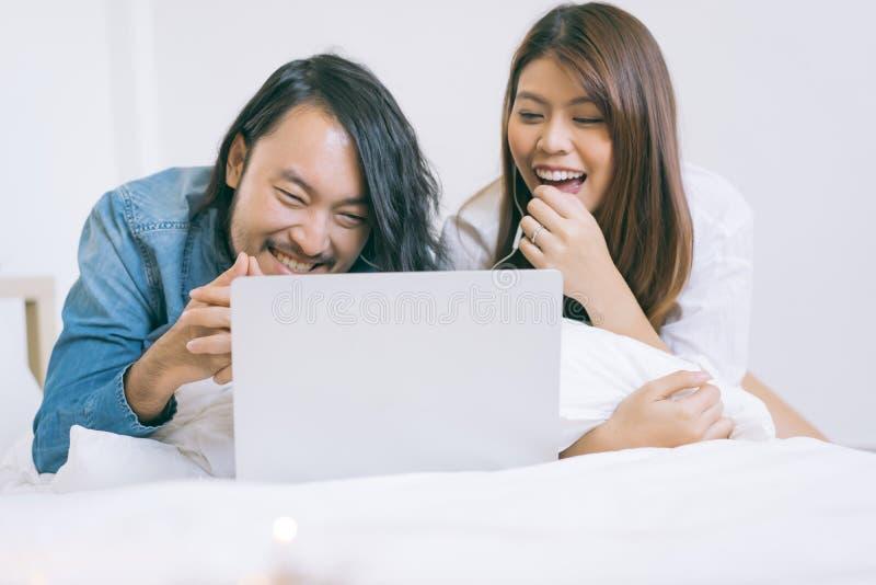 Молодые азиатские пары смотря фильм с ноутбуком в кровати стоковые фото