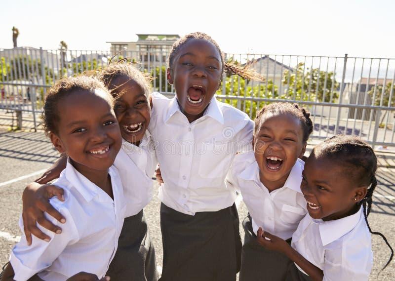 Молодые африканские школьницы в спортивной площадке усмехаясь к камере стоковая фотография rf