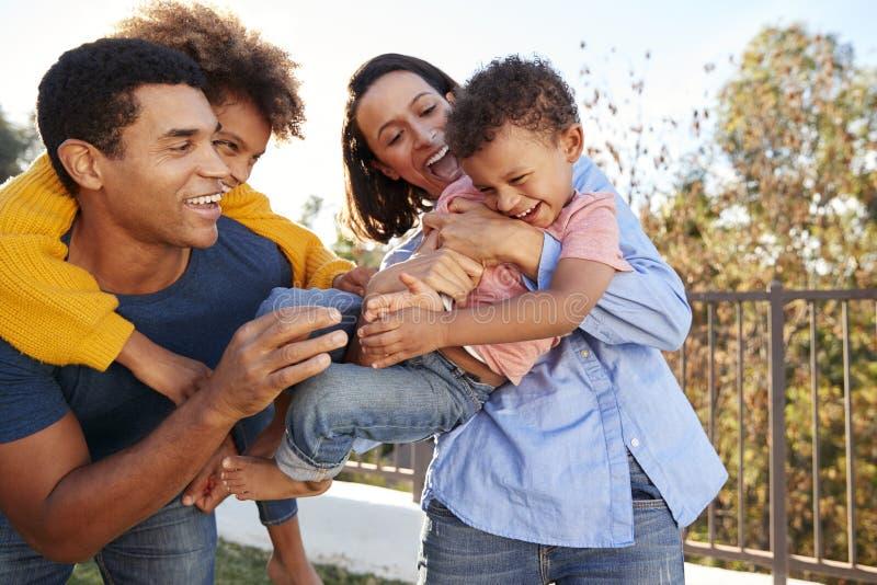 Молодые Афро-американские родители играя outdoors носить их детей в саде стоковая фотография rf