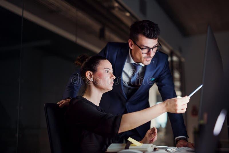 Молодые бизнесмены в офисе вечером, используя компьютер стоковое изображение