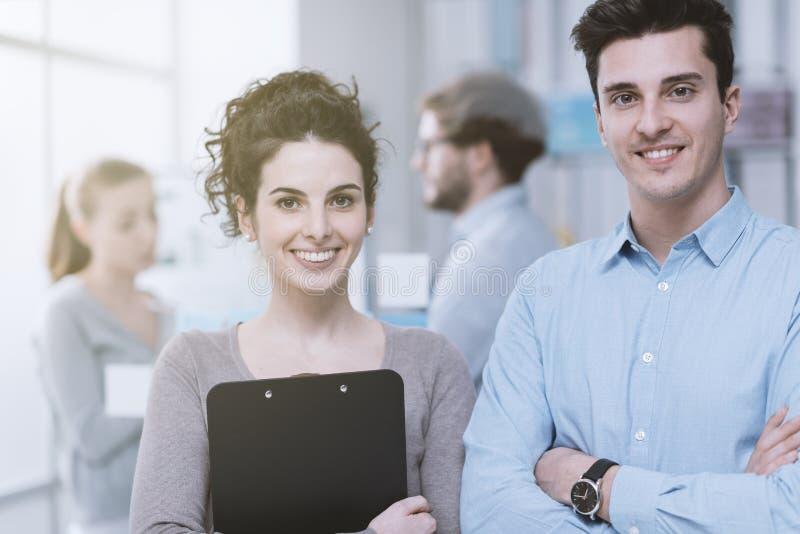 Молодые бизнесмены в офисе стоковые изображения