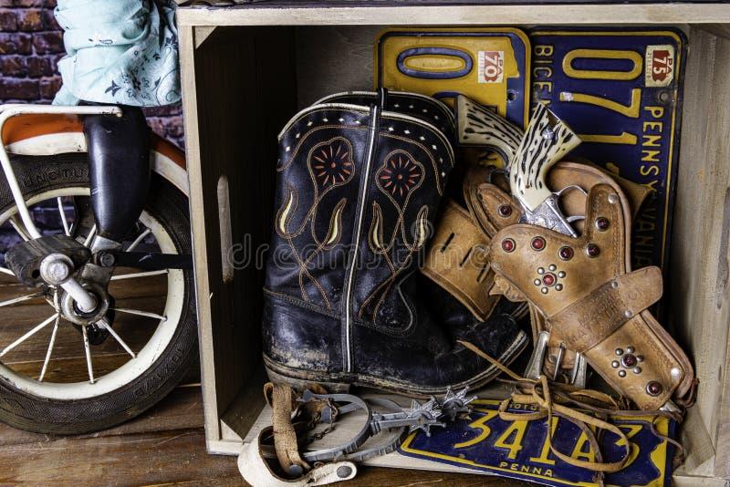 Молодые ботинки и оружи ковбоя коробки сокровища мальчиков стоковое изображение