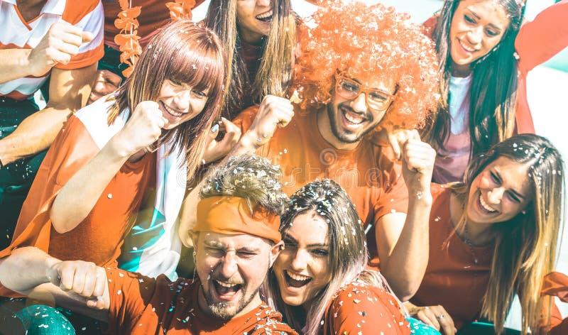 Молодые вентиляторы сторонника футбола веселя со спичкой чашки футбола флага и confetti наблюдая на стадионе - группе людей друзе стоковое фото rf