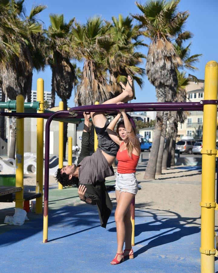 Молодые взрослые играя в спортивной площадке детей стоковое изображение