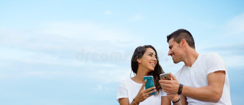 Молодые датировка пар и использовать smartphones совместно стоковые изображения