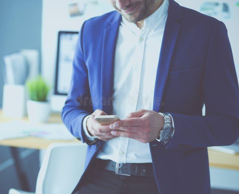 Молодые дизайнерские писать sms в его офисе стоковое изображение