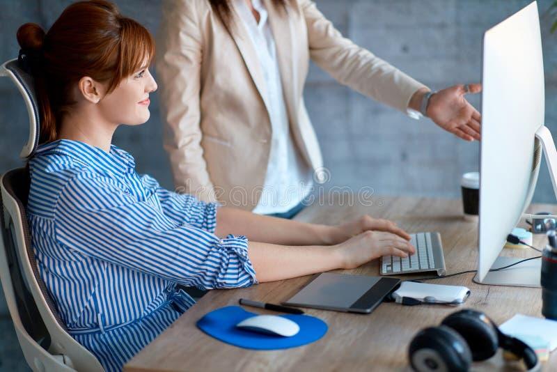Молодые дизайнеры перспективы работая в офисе с компьютерами стоковое изображение