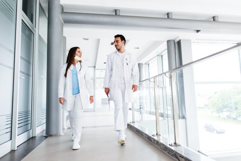 Молодые доктора идя совместно через больницу крытую стоковое фото rf