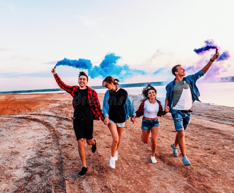 Молодые друзья бежать с пирофакелом или fusee руки стоковая фотография