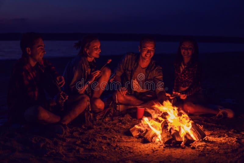 Молодые друзья имеют пикник с костром на пляже стоковое изображение