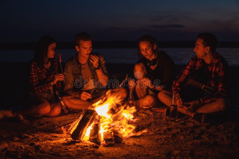 Молодые друзья имеют пикник с костром на пляже стоковое фото rf