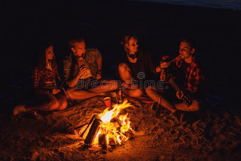 Молодые друзья имеют пикник с костром на пляже стоковые фотографии rf