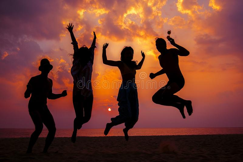 Молодые друзья имея потеху на пляже и скача против фона захода солнца над морем стоковое фото rf