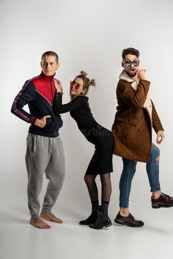 Молодые друзья имея потеху совместно, красивая женщина стоя между 2 красивыми людьми стоковые фотографии rf