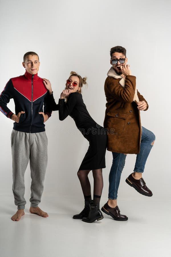 Молодые друзья имея потеху совместно, красивая женщина стоя между 2 красивыми людьми стоковое фото rf
