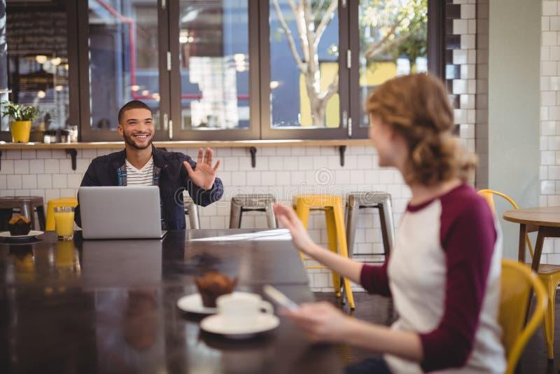 Молодые друзья развевая пока сидящ на кофейне стоковое фото