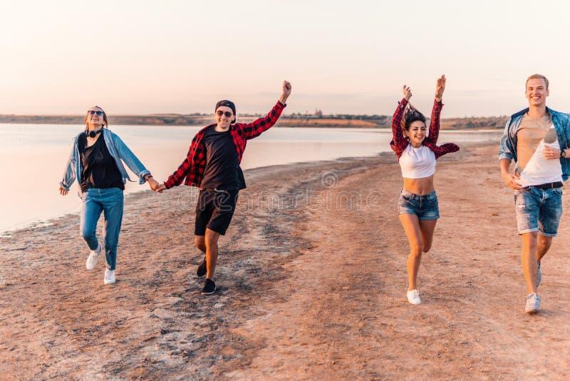 Молодые друзья хипстера на пляже бежать совместно стоковое изображение rf