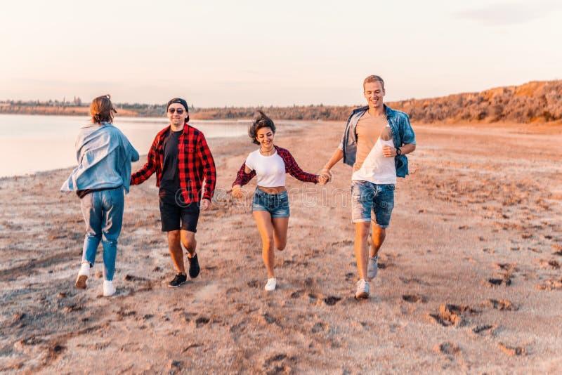 Молодые друзья хипстера на пляже бежать совместно стоковое изображение