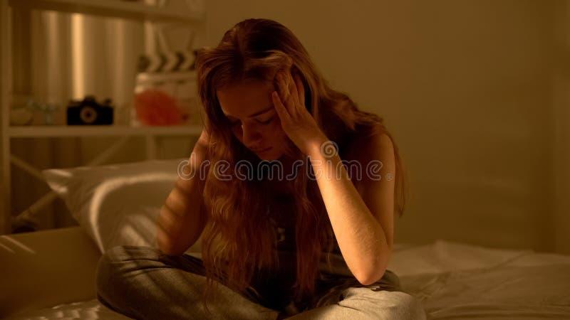 Молодые женские держа виски сидя в доме кровати, страдая депрессии полового созревания стоковое фото rf