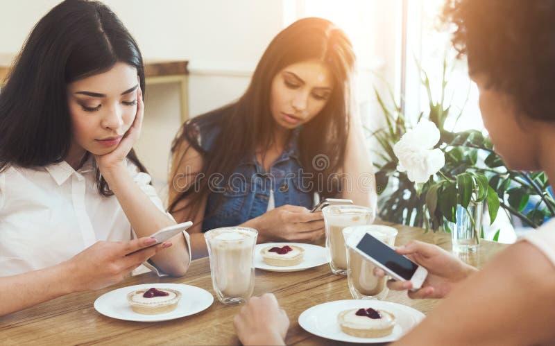 Молодые женские друзья используя телефоны и чувствовать бурящ совместно стоковые фото