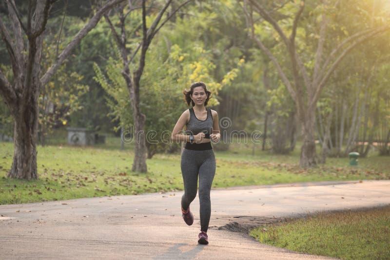Молодые женщины бегуна jogging на дороге с предпосылкой захода солнца Healt стоковое фото