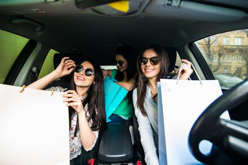 Молодые женщины возвращающ от покупок внутри автомобиля Маленькие девочки ехать автомобиль и возвращающ от покупок стоковые изображения rf