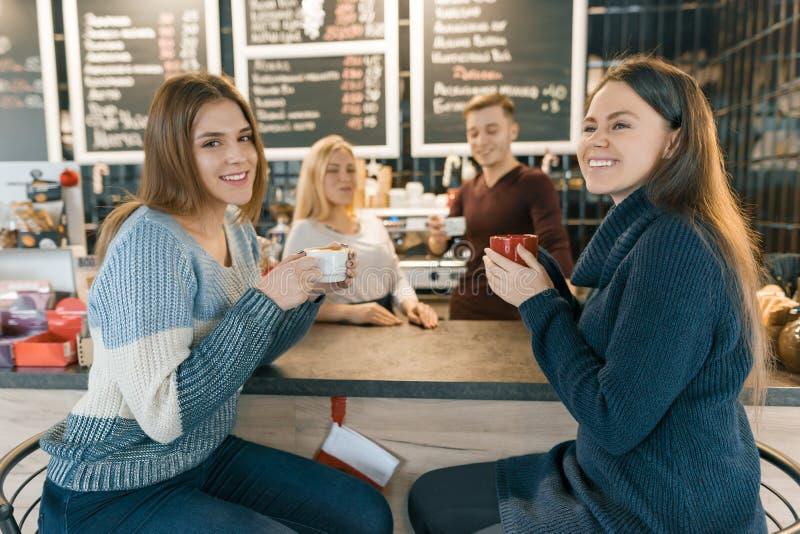 Молодые женщины выпивая кофе в кафе, девушках сидя около счетчика бара, barista предпосылки работая делая кофе стоковое фото