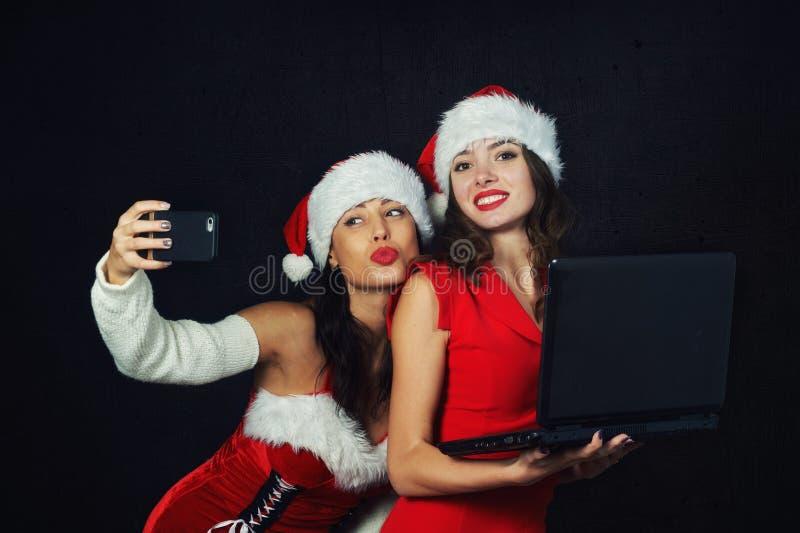 Молодые женщины в шляпах Санта с ноутбуком и телефоном стоковое изображение rf