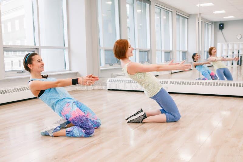 Молодые женщины делая разминку в тренажерном зале внутри помещения для того чтобы освободить вес стоковое фото rf