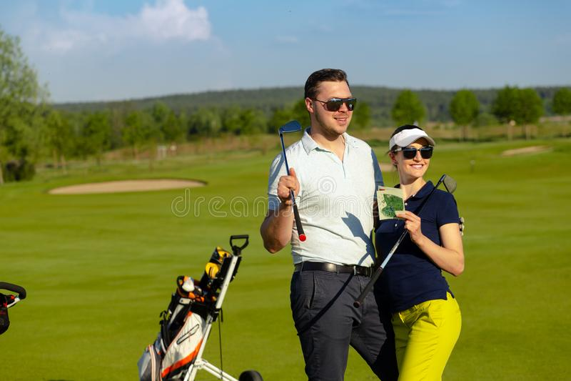 Молодые женщины и люди играя гольф на солнечном дне стоковое фото rf