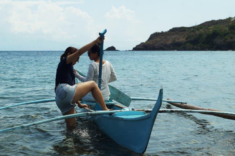 Молодые женщины наслаждаются ехать на крошечной маленькой лодке на море стоковые изображения