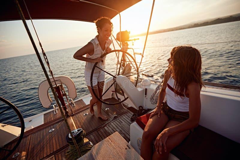 Молодые женщины плавая на роскошной шлюпке совместно и насладиться на заходе солнца стоковая фотография